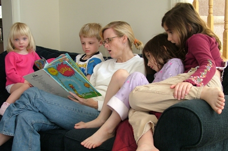 Au_Pair_and_three_kids_reading_a_book